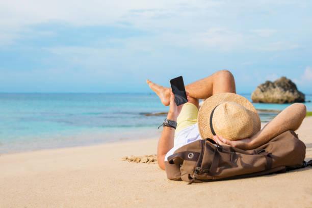 adam sahilde yalan smartphone ile - yatmak stok fotoğraflar ve resimler