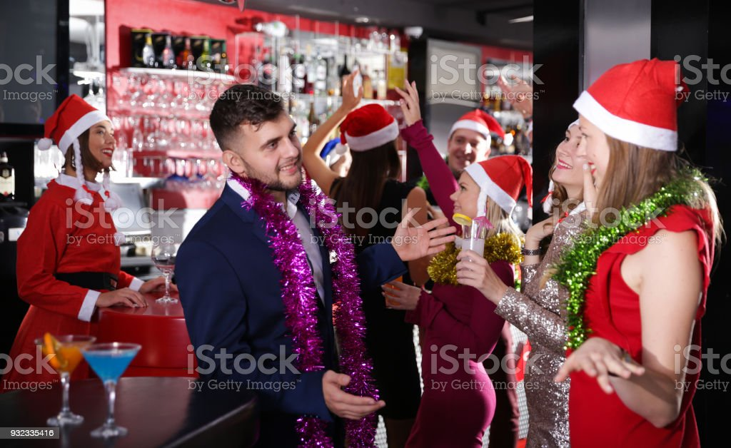 Guy with two girls on new year party in bar stock photo