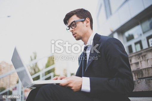 Young businessman working on his laptop infront of his office building while sitting on the stairs.
