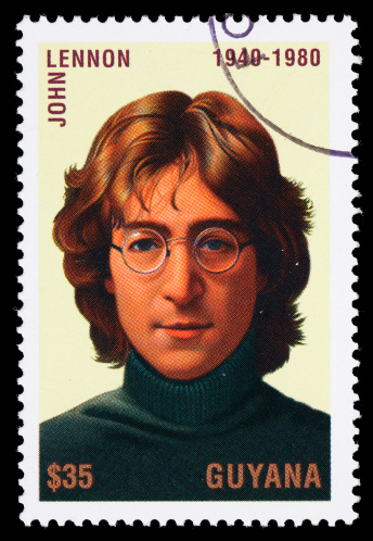 Sacramento, California, USA - April 15, 2011: A 1995 Guyana  postage stamp with a portrait of John Lennon (1940-1980). Lennon was a singer and songwriter, writing or co-writing more than two dozen number one hits, most of them while a member of The Beatles.