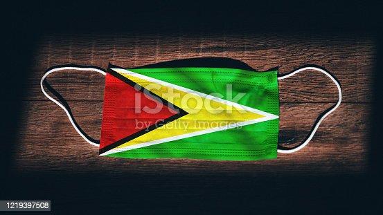 istock Guyana National Flag at medical, surgical, protection mask on black wooden background. Coronavirus Covid