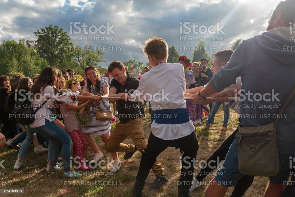 Guys and girls pull the rope at the celebration of the folk festival of Ivan Kupala stock photo
