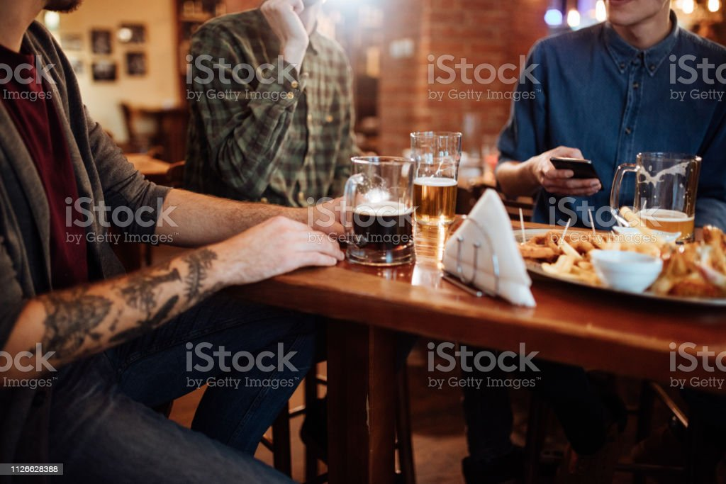 Guys at Pub Drinking Beer and Looking at Smartphone stock photo