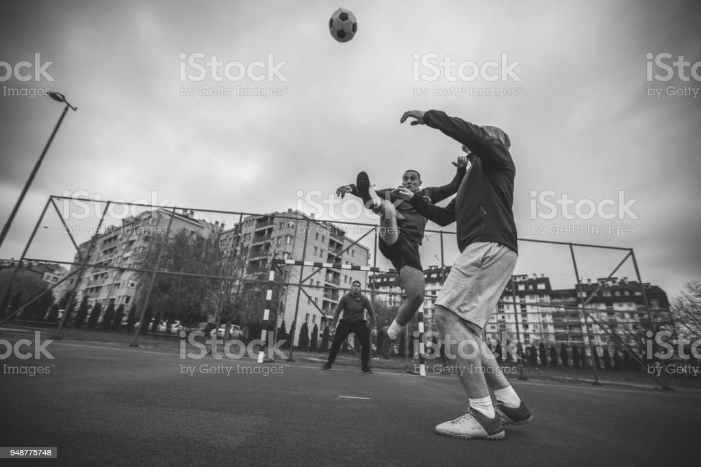 Guys playing soccer outdoors stock photo