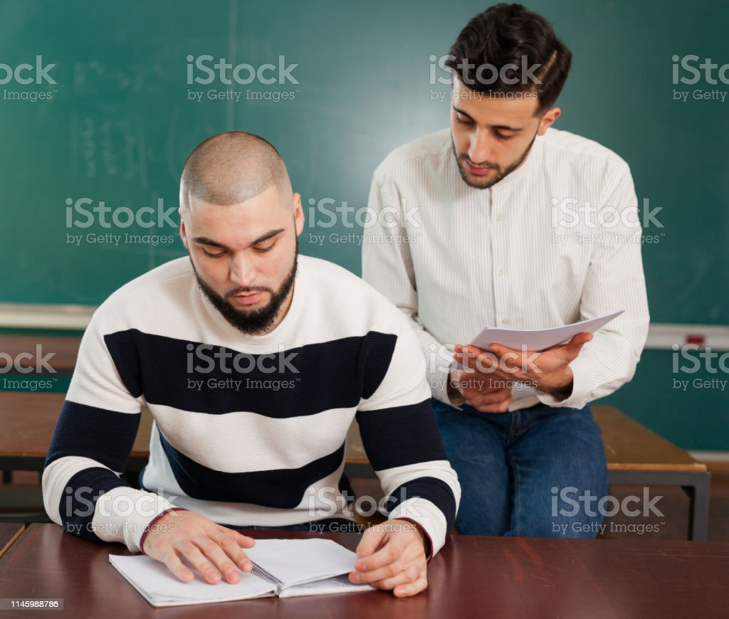 Portrait of two young guys working on their student project at desk...