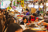 Photo taken in food market Gwangjang in Seoul, South Korea. candid photo of people enjoying lunch at a local food stall. Shop owners serving customers. Portrait of typical everyday life in Korea