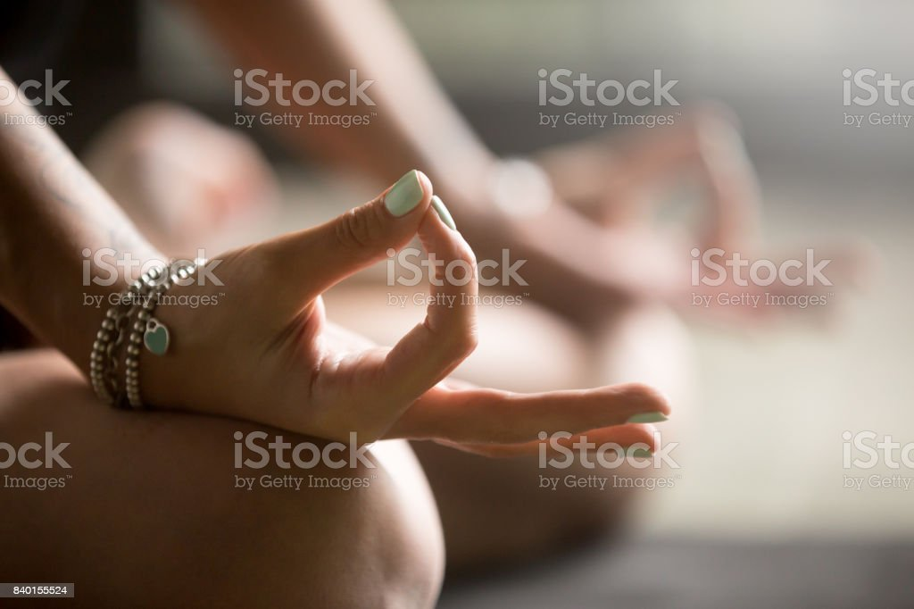 Gyan mudra close up image Gyan mudra close up, woman joining together the tip of index finger with thumb, wearing wrist bracelets, practicing yoga in concentration pose, stress relieve exercise at home, focus on right hand Yoga Stock Photo