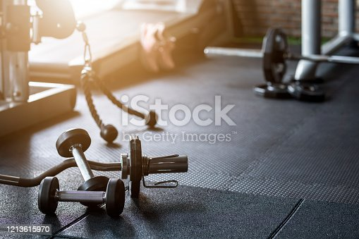 Gym background Fitness weight equipment on empty dark floor