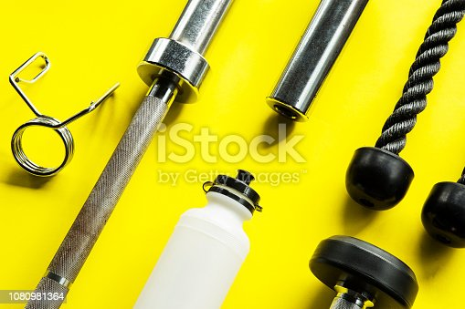 istock Gym background with Fitness equipment for workout gym on isolated yellow background 1080981364