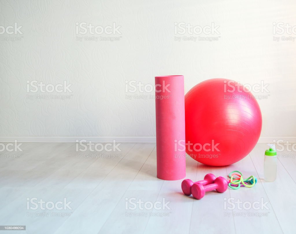 Gym ball, yoga mat, skipping rope, dumbbell  and bottle of the water closeup on white background stock photo
