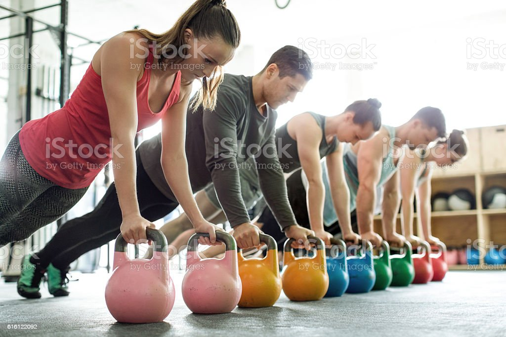 Gym class doing push-ups on kettlebells stock photo