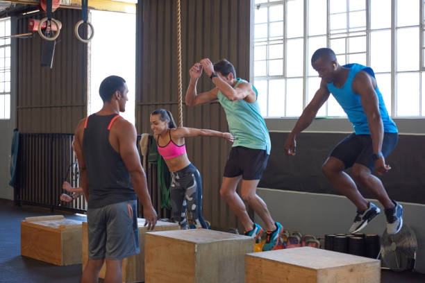 gym class jumping on wooden boxes guided by trainer - jumping zdjęcia i obrazy z banku zdjęć