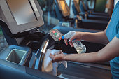 istock Gym cleaning and disinfection. Infection prevention and control of epidemic. Staff using wipe and alcohol sanitizer spray to clean treadmill in gym. Anti Covid-19 precautions 1224155022