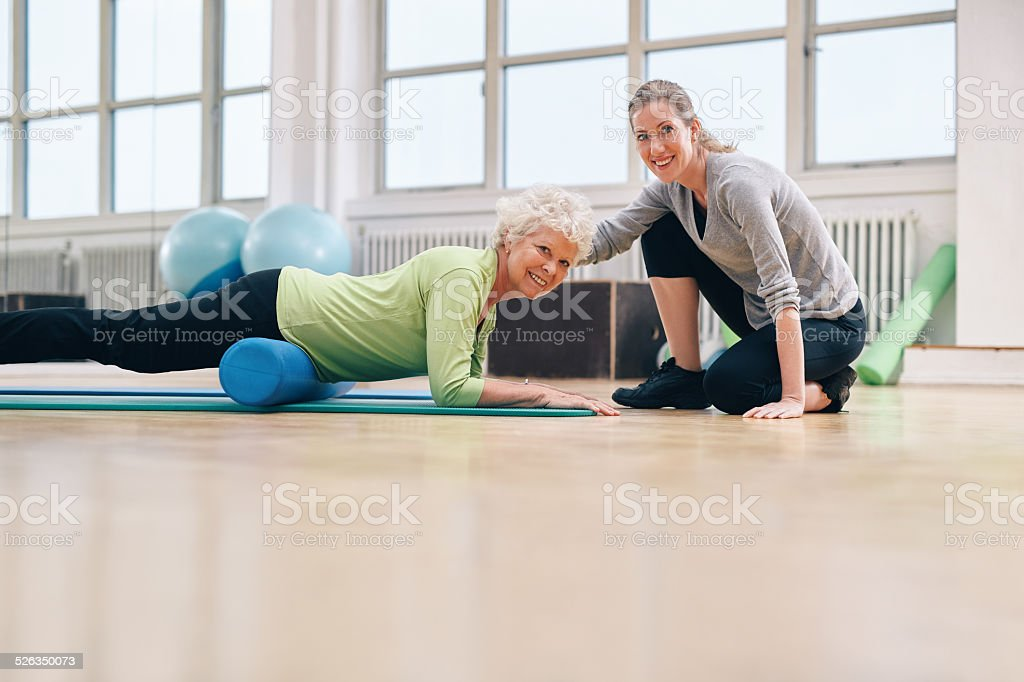 Gym coach helping elderly woman in her workout stock photo