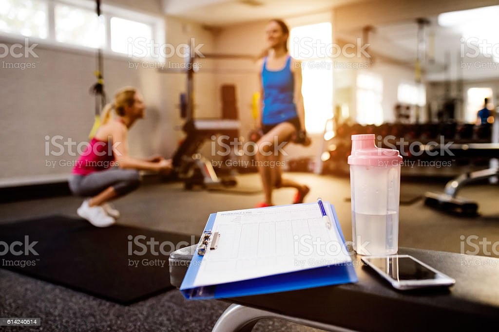 Gym details, women exercising, clipboard, water bottle, smart ph stock photo