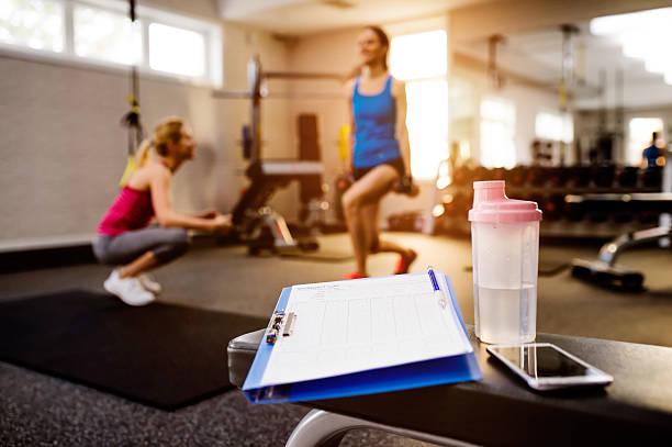 gym details, women exercising, clipboard, water bottle, smart ph - trainingsplan frauen stock-fotos und bilder