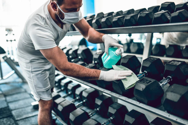 Gym Disinfection By Male With Face Mask Gym Disinfection By Male With Face Mask gym stock pictures, royalty-free photos & images