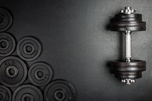 gym dumbbells with black metal weights 1kg and 2kg on black background with copy sapce, photograph taken from above. - peso foto e immagini stock