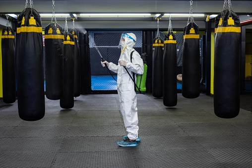 A mid adult woman in protective gear disinfecting a gym.
