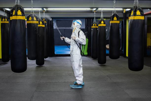 Gym employee wearing PPE and disinfecting everything stock photo