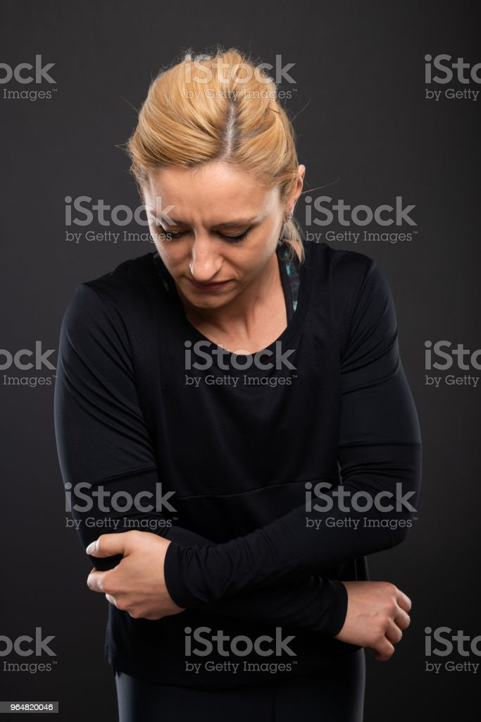 Gym female trainer holding elbow like hurting royalty-free stock photo
