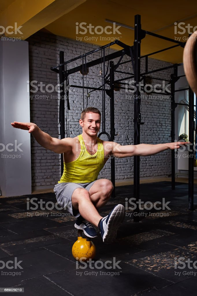 gym fitness man standing on one leg and balance on the kettlebells in...