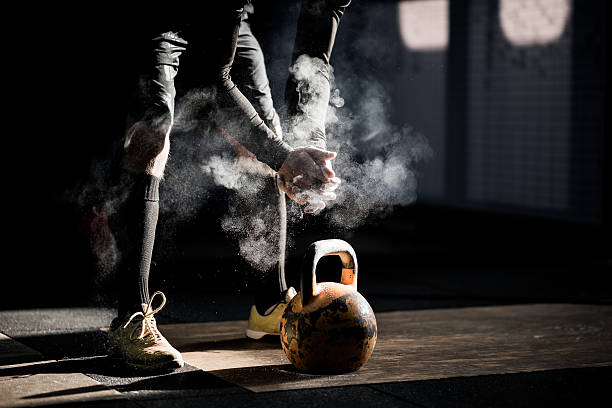 gym fitness workout: man ready to exercise with kettle bell - health club stock photos and pictures