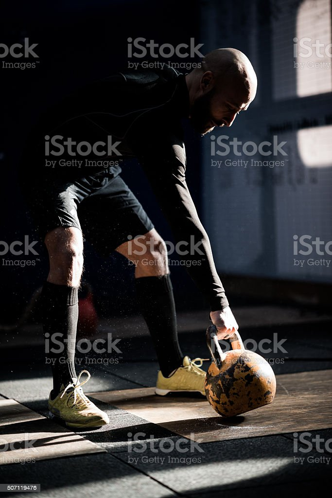 Gym fitness workout: Man ready to exercise with kettle bell stock photo