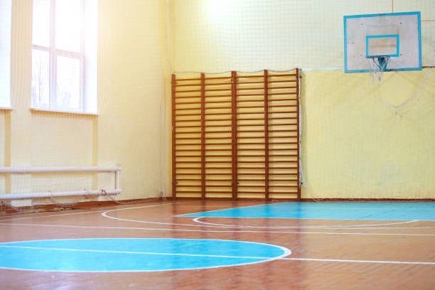 Gym for sports classes at school or College. Swedish wall, stairs, and wooden floor with markings for volleyball. stock photo