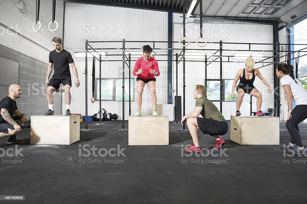 gym group trains box jump stock photo