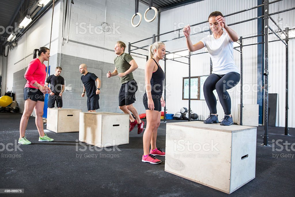 gym group trains box jumps stock photo
