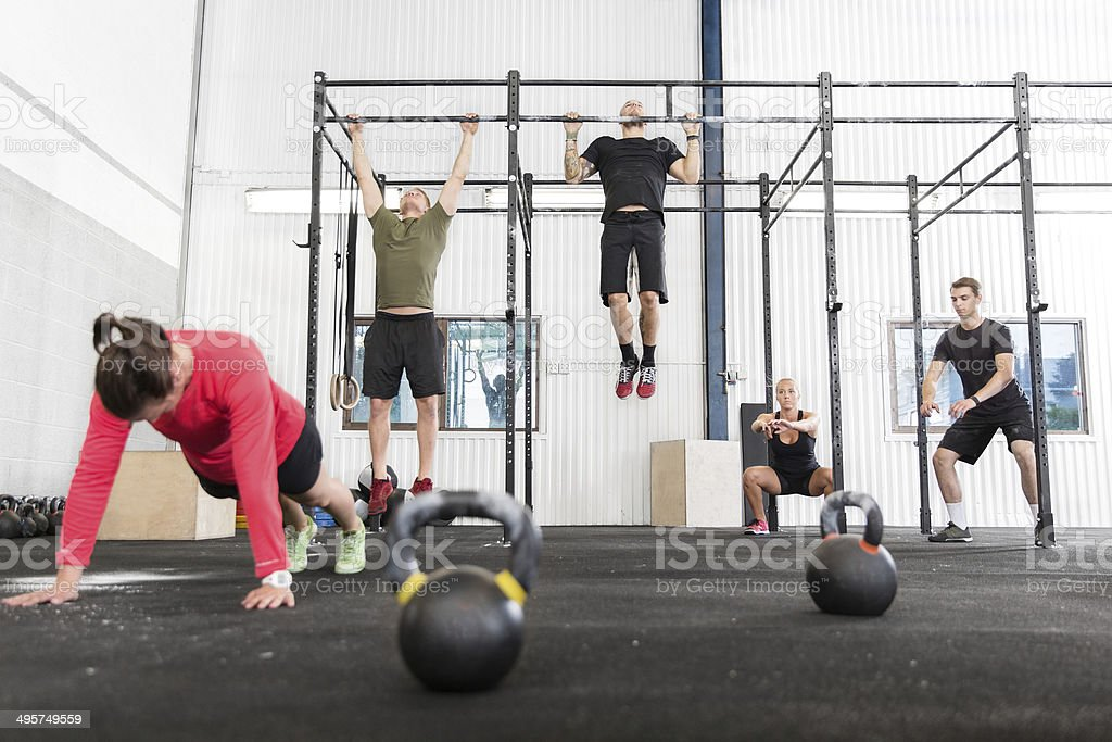 gym group trains different exercises stock photo