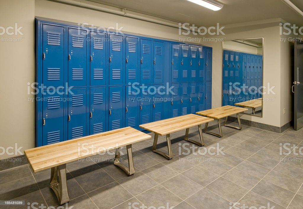 Gym locker room with wooden benches and blue lockers stock photo