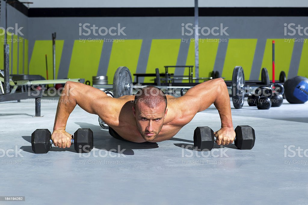 Gym man push-up strength pushup exercise with dumbbell royalty-free stock photo