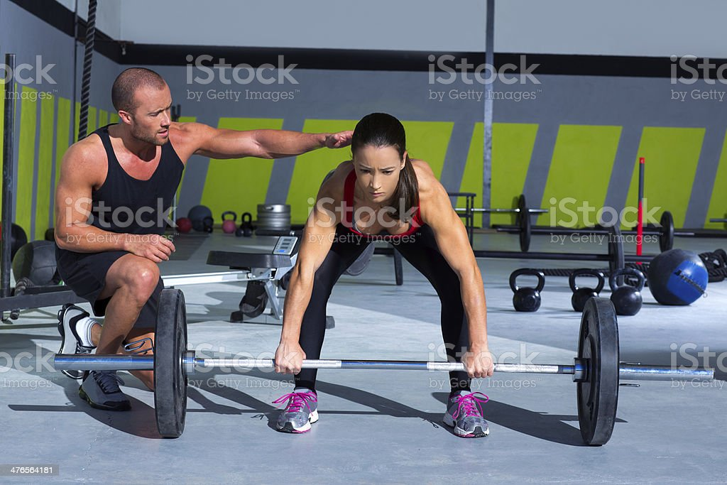 gym personal trainer man with weight lifting bar woman royalty-free stock photo