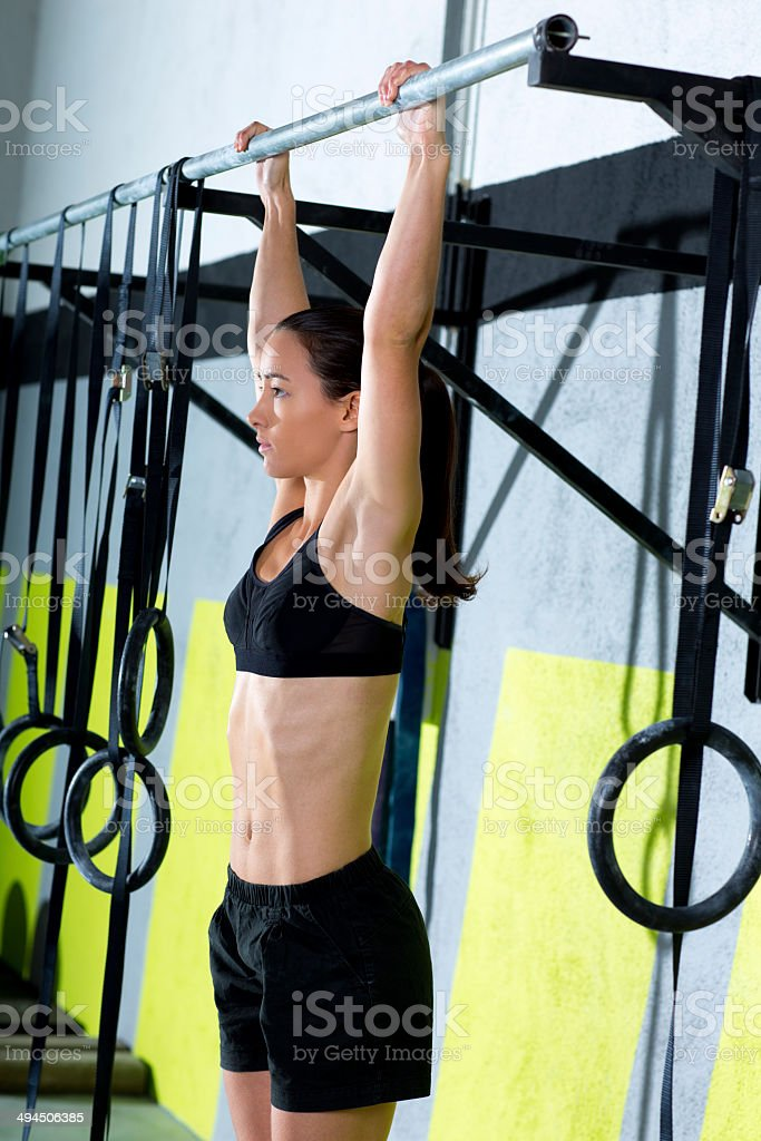 gym toes to bar woman pull-ups 2 bars workout stock photo