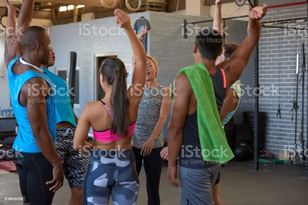 Gym trainer bringing everybody in for group cheer stock photo