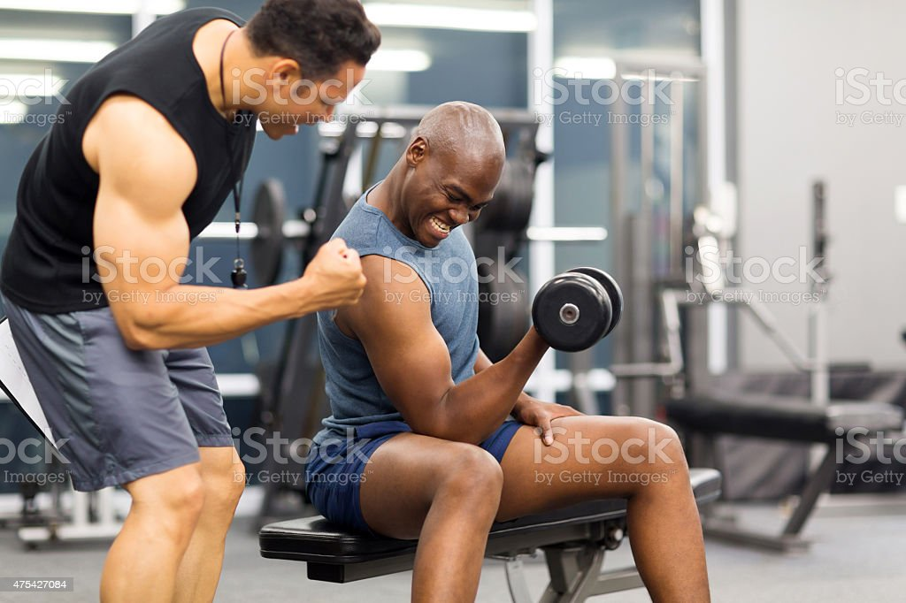 gym trainer motivating client to lift dumbbell stock photo