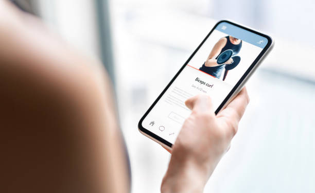 Gym training app in phone. Online personal trainer or video tutorial mockup in smartphone. Home workout with fitness class or digital sport coach. Exercise instruction. Getting fit. stock photo