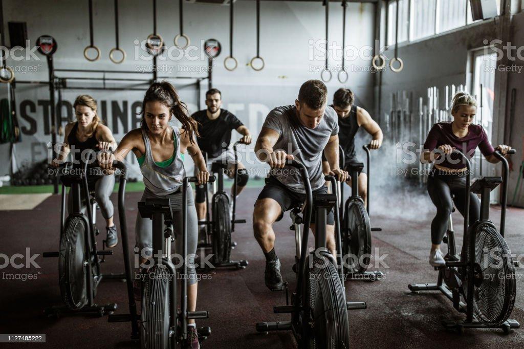 Cruz apto treinamento em bicicletas estacionárias! - Foto de stock de Academia de ginástica royalty-free