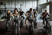 Large group of athletic people having sports training on exercise bikes in a gym