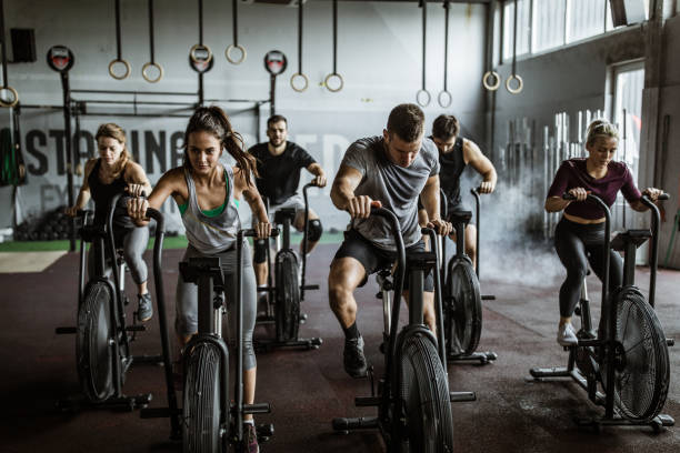 gym training on stationary bikes! Large group of athletic people having sports training on exercise bikes in a gym endurance stock pictures, royalty-free photos & images
