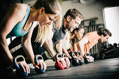 gym personal trainer doing push ups on kettle bells with small group of people in Gym.