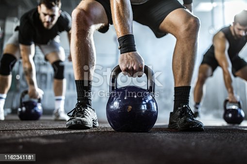 Unrecognizable athletic man and his friends having strength training with kettle bells in a gym. Copy space.