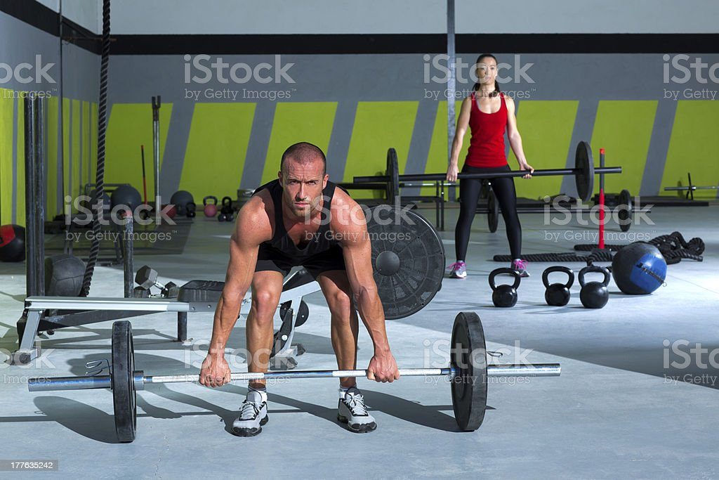 gym with weight lifting bar workout man and woman royalty-free stock photo