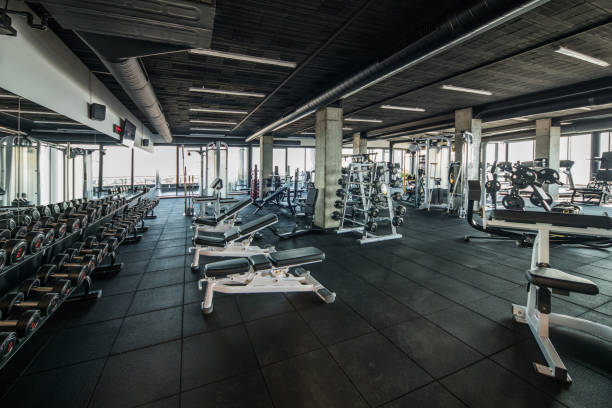 Gym without people with large group of exercise machines. Large group of exercise machines and equipment in a gym. exercise machine stock pictures, royalty-free photos & images