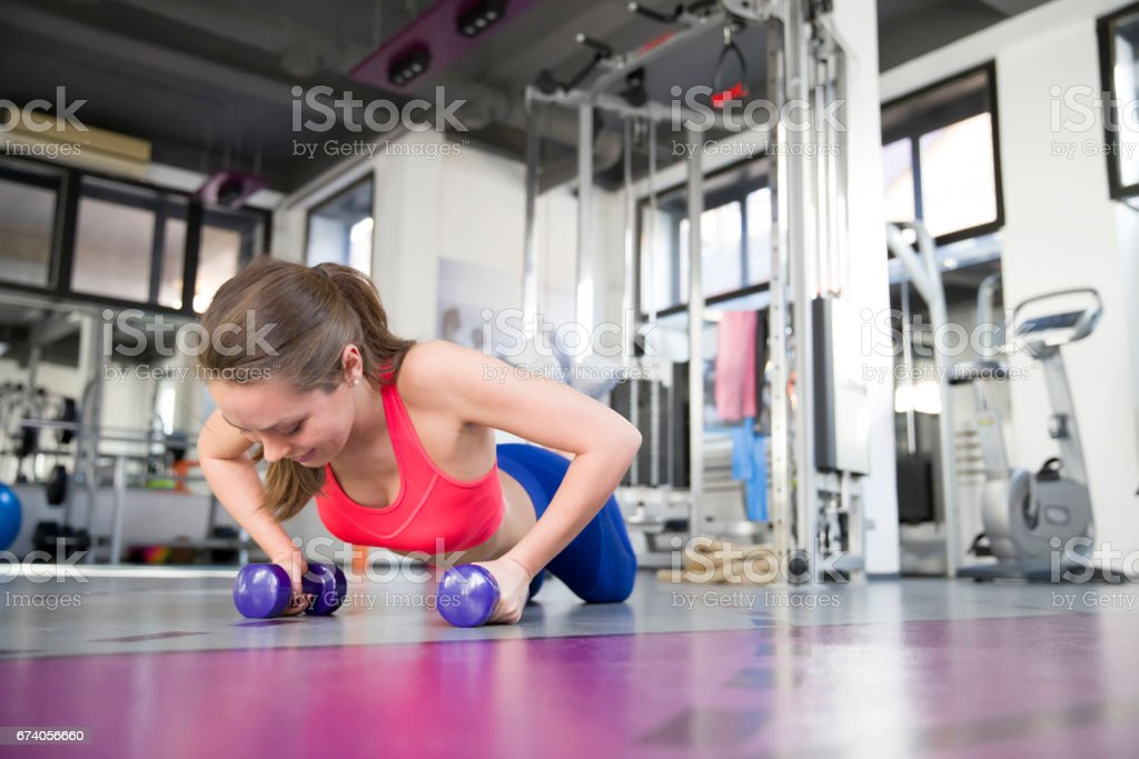 Gym woman doing pushup exercise with dumbbell in a gym royalty-free stock photo
