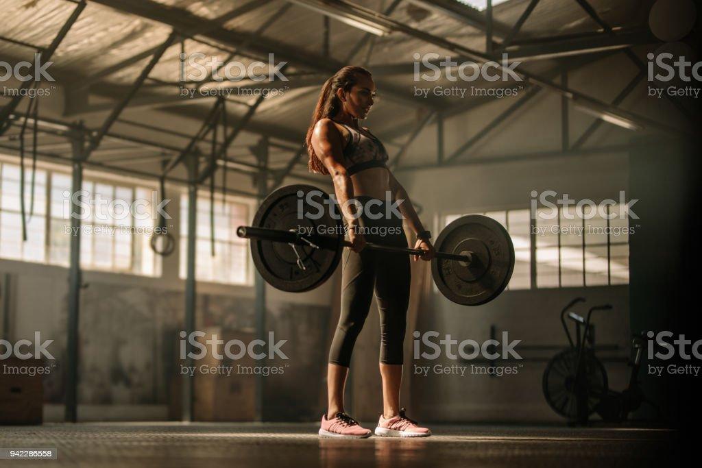 Cruz apta mulher levantando pesos pesados no ginásio - Foto de stock de Academia de ginástica royalty-free