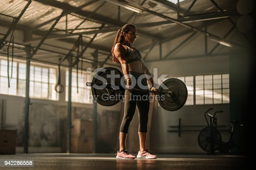 Strong female athlete holding a barbell in her hands. gym woman lifting heavy weights in gym.