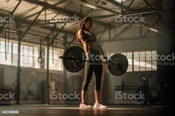Foto de Cruz Apta Mulher Levantando Pesos Pesados No Ginásio e mais fotos de stock de Academia de ginástica